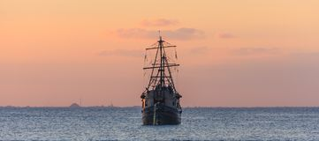 Old Sailboat sailing under sunset in the Caribbean Sea. Old wooden sailboat at sunset in the Caribbean sea. Beautiful sky color at twilight. Blue water. Front royalty free stock photo