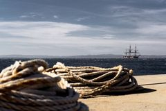 Old wooden sailboat with three masts anchored offshore stock images