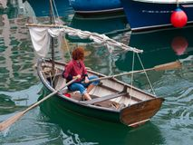 Old wooden sailing boat in the port of Bermeo. Old wooden sailing boat and a girl paddling in the port of Bermeo. Bizkaia Basque Country Royalty Free Stock Photo
