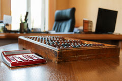 Old wooden scores and modern calculator Royalty Free Stock Photo
