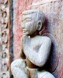 Old wooden sculpture. Greeting position at old palace of Mandalay, Myanmar Stock Photos