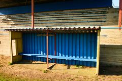 Old wooden seats on outdoor stadium players bench, chairs with worn paint below rusty metal sheets roof. Autumn poor grass Stock Image