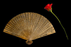 Old wooden shed fan with a red rose. On a black background Stock Photo