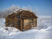An old wooden shed with a thatched roof. Covered with snow, the bright winter's day, blue sky Royalty Free Stock Photos