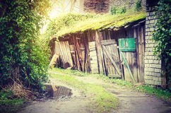 Old wooden sheds in lane. Scenic view of old wooden sheds or stables in rural lane with colorful sunshine Stock Photography