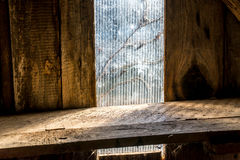 Old wooden shelf in loft in front of window. Old wooden shelf in loft in front of plastic window Royalty Free Stock Image