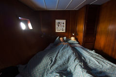 Old wooden ship cabin interor, sleeping woman in bed. Sleeping woman lays in dark cabin in nautical vessel Stock Photo