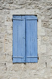 Old wooden shutters pained blue. Closed wooden shutters in a stone wall Royalty Free Stock Photos
