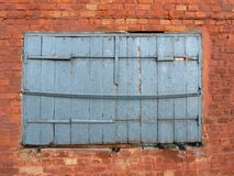Old wooden shutters. In the wall of red brick Royalty Free Stock Images
