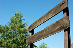 Old wooden sign. Old faded wooden sign with tree in background against blue sky Stock Photo