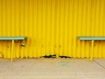 Old wooden sits on outdoor stadium players bench, chairs bellow old worn roof Stock Image