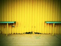 Old wooden sits on outdoor stadium players bench, chairs bellow old worn yellow roof. Royalty Free Stock Images