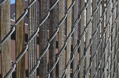 Old wooden slats in the chain linked fence. A few old long wooden slats inside the metal chain linked fence in the back warehouse are royalty free stock photo
