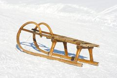Old wooden sledge. With snow in background royalty free stock images