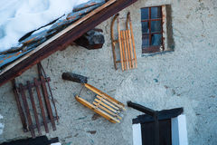 Old, wooden sleds on a woll of a old chalet Stock Photo