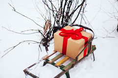 Old wooden sleigh with a gift in golden paper box wrapped red gift ribbon, are in the winter forest, snow, trees near. Wooden sled Royalty Free Stock Images