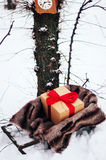 Old wooden sleigh with a gift in golden paper box wrapped red gift ribbon, are in the winter forest, snow, trees near. Wooden sled Stock Photography