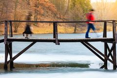 Old, wooden, small bridge on frozen lake Royalty Free Stock Image