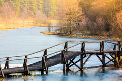 Old, wooden, small bridge on frozen lake Stock Photography