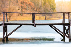 Old, wooden, small bridge on frozen lake Stock Images