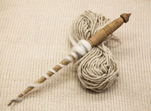 Old wooden spindle with a ball of wool thread for the manufacture of woolen threads on a tissue background Stock Photos