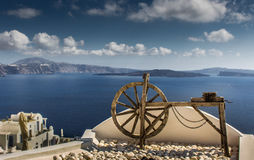 Old wooden spindle wheel on a roof. An old spindle on a roof with the Santorini landscape background, Greece Stock Photography