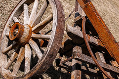 Old wooden spoked wagon wheel,frame. Close-up of an old weathered antique wooden wagon frame and spoked wheel Royalty Free Stock Images