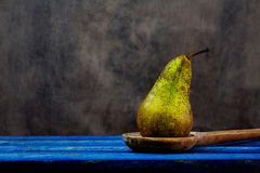 Old wooden spoon pear blue boards Stock Photo