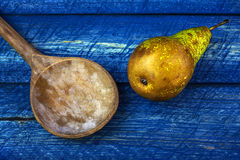 Old wooden spoon pear blue boards Royalty Free Stock Photography