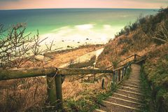 Old wooden stair way down with wooden hadrail, steps  down to  sea shore hill Royalty Free Stock Image