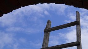 An old wooden staircase against a blue sky and clouds. Framed by a round arch Royalty Free Stock Photo