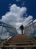 Old wooden staircase with wide steps and metal railing, stretching into the blue sky with huge white cloud, up the stairs a man ru Stock Images