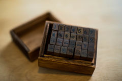 Old wooden stamp. In wooden box on table stock photos