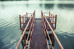 Old wooden and steel made jetty on the lakeside. Old wooden and steel made jetty floating on the lakeside Royalty Free Stock Images