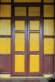 Old wooden style doors with mustard yellow painted color Royalty Free Stock Photo
