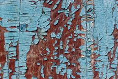 Old wooden surface in a brown colour with pieces of peeling blue. Paint. Background, texture Stock Photos