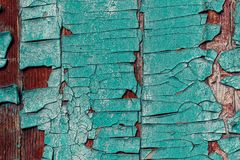 Old wooden surface in a brown colour with pieces of peeling blue. Turquoise paint. Close up. Background, texture Stock Photos