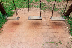 Old wooden swing. On the playground in the park royalty free stock image
