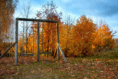 Old wooden swing in the autumn forest Stock Photo