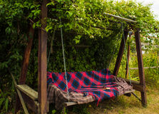 Old wooden swing in the green garden. Stock Images