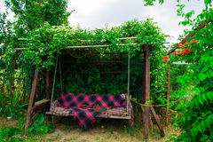 Old wooden swing in the green garden. Stock Photos