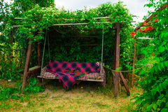 Old wooden swing in the green garden. Stock Image