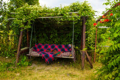 Old wooden swing in the green garden. Royalty Free Stock Photos