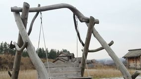 Old wooden swing hanging on ropes at open-air history and folklife museum. Stock footage stock video footage