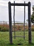 Old wooden swing on the lake background. Old country swing. Retro. Kizhi Pogost on Kizhi Island, Onega Lake, Karelia. royalty free stock images