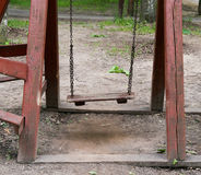 An old wooden swing. An old wooden swing in a lush backyard Stock Photos