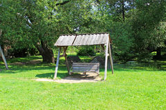 Old wooden swing in the park. On a sunny day Stock Image