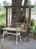 Old wooden swing with the white tabel. Old wooden swing with the white tabel near the local road of the small coffee shop Stock Photo