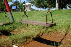 Old wooden swings. In the playground Stock Photos