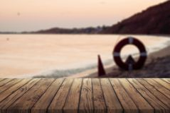 Old wooden table for advertising your products, wooden table against the sea at sunset. The concept of marine rescuers stock photos